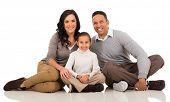 portrait of cute young family sitting on white