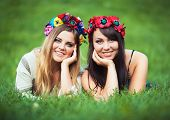 Two Laughing Girl In Ukrainian National Costumes Lie On The Green Grass