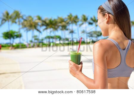 poster of Woman drinking vegetable Green detox smoothie after fitness running workout on summer day. Fitness a
