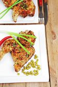 roast chicken : legs garnished with green peas , peppers , and cutlery on white plates over wooden table