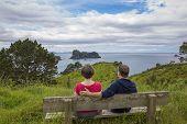 Man and woman enjoying a beautiful ocean view in New Zealand