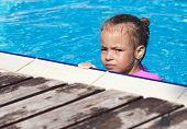 Upset little girl swimming in the pool.