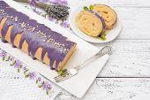 Sponge roll with lavender custard cream on wooden background