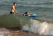 Dad catches child riding a wave of the sea.