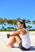 Exercise woman runner drinking green vegetable smoothie resting and relaxing after running.  Fitness and healthy lifestyle concept with multiracial Asian Caucasian female model.