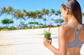 stock photo of summer beach  - Woman drinking vegetable Green detox smoothie after fitness running workout on summer day - JPG