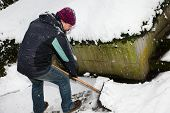 image of snow shovel  - a man is snow shoveling the snowy path - JPG