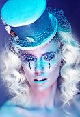 Close up Pretty Young Woman, with Wavy Blond Hair, Wearing Futuristic Make-up with Stylish Hat, Looking at the Camera. Captured at Studio with Blue Violet Background.