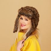Pretty young woman in stylish winter fashion wearing an elegant bright yellow top and fur hat turning to give the camera a charming smile