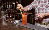 Bartender is decorating cocktail with slice of bell pepper, toned image