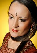 Young beautiful woman in indian traditional jewellary bindi and sari dress. yellow background