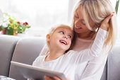 stock photo of daughter  - Mother and daughter using tablet computer together at home - JPG