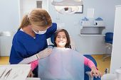 Pediatric dentist examining her smiling young patient in dental clinic