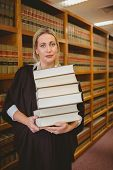 Lawyer holding heavy pile of books standing in library