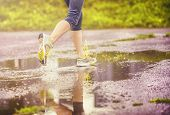 foto of rainy weather  - Young woman jogging on asphalt in rainy weather - JPG