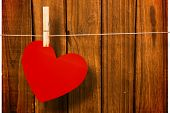 Heart hanging on line against overhead of wooden planks