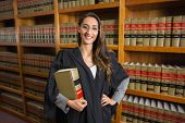 foto of laws-of-attraction  - Pretty lawyer looking at camera in the law library at the university - JPG