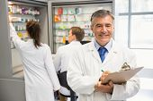 stock photo of clipboard  - Senior pharmacist writing on clipboard at the hospital pharmacy - JPG