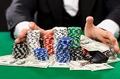 casino, gambling, people and entertainment concept - close up of poker player with chips, money and personal stuff at green casino table