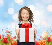people, childhood, summer and holidays concept - happy smiling girl with gift box over poppy field background