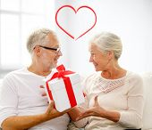 family, holidays, christmas, age and people concept - happy senior couple holding gift box over white room background with red heart shape