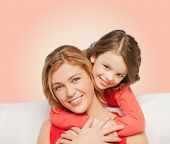 people, love, holidays, family and motherhood concept - happy mother and daughter hugging over pink background