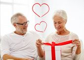 family, holidays, christmas, age and people concept - happy senior couple opening gift box over white room background with red heart shapes