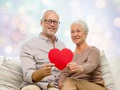 family, holidays, age and people concept - happy senior couple holding little red paper heart shape cutout and sitting on sofa over blue lights background