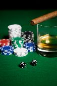 gambling, fortune and entertainment concept - close up of casino chips, whisky glass, dice and cigar on green table surface