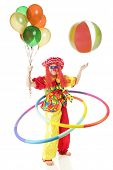 A happy clown in wild patterns and colors twirling 2 hula hoops while holding a balloon bouquet and bouncing a beach ball in the air.  Motion blur on hoops, ball and left hand.  On a white background.