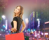 people, holidays and sale concept - young happy woman with shopping bags over night city street background