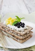 picture of mountain-ash  - rye bread with cottage cheese black berries of mountain ash and mango on a white wooden background - JPG