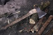 image of firewood  - Old axe and firewood against a dark background - JPG