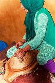 Female worker grinding Argan nuts