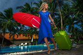 Pretty girl in blue dress and modern hairstyle dreadlocks with a green suitcase and surfboard on a resort