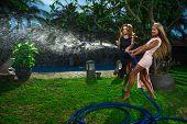 Beautiful women having fun with garden hose splashing summer rain.
