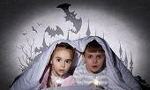 Children sitting in bed under blanket with flashlights