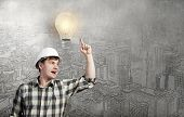 Young man builder pointing at light bulb. Idea concept