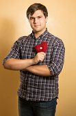 Man In Checkered Shirt Holding Decorative Red Heart