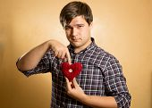 Portrait Of Hipster Man Pointing On Red Knitted Heart