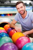 image of bowling ball  - Cheerful young man sitting near bowling balls and smiling against bowling alleys - JPG