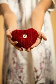Red Knitted Heart Lying On Girls Stretched Hands
