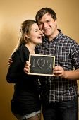 Couple In Love Holding Blackboard With Written Word