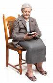 Senior woman using mobile phone sitting on chair