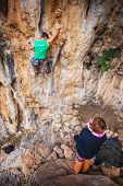 Man lead climbing on a cliff, belayer watching him