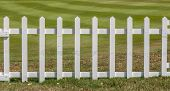 pic of farm land  - White wooden fence in farm field marks for land property - JPG