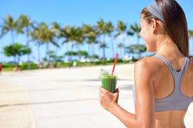 picture of smoothies  - Woman drinking vegetable Green detox smoothie after fitness running workout on summer day - JPG