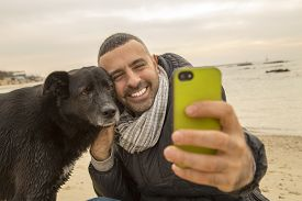 stock photo of nonverbal  - Man helping his dog making selfie image using a smartphone - JPG