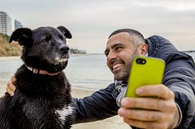 picture of nonverbal  - Man helping his grumpy dog firend to take a social media selfie image using a smartphone - JPG