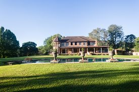 stock photo of mansion  - Scenic countryside home mansion landscape with open lawn trees swimming pool - JPG